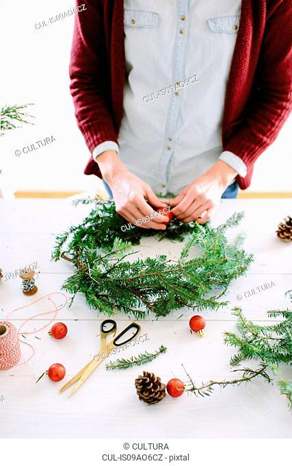 Woman decorating Christmas wreath