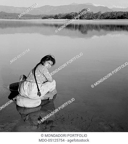 Nepalese young woman sitting on a rock by the lake. Nepal, 1965
