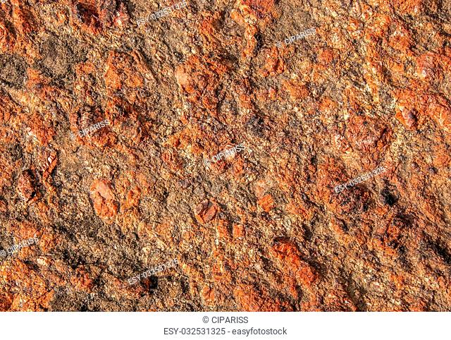 Abstract background of red granite with a rough surface