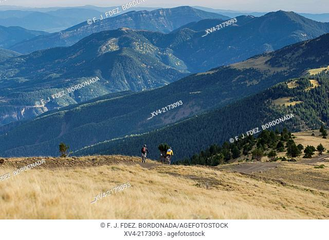 Bikers on action riding down on the Valley of Buesa. Sobrarbe, Pyrenees, Huesca