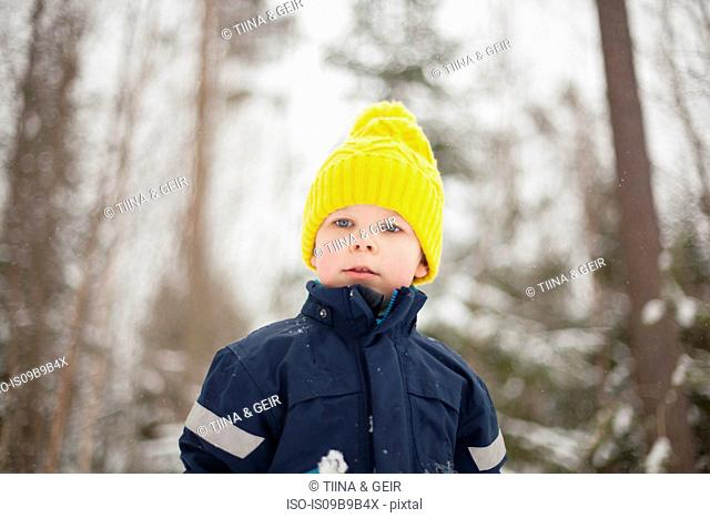 Boy in yellow knit hat in snow covered forest
