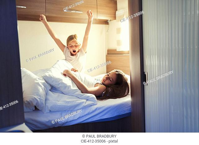 Sisters waking and stretching on bed in motor home