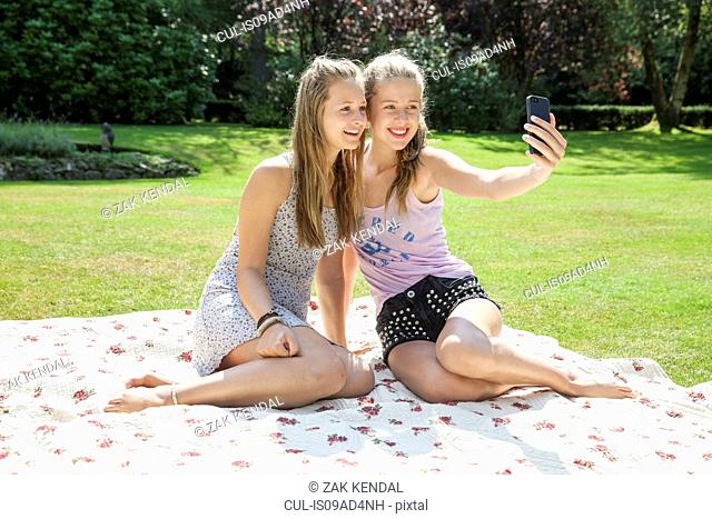 Two teenage girls on picnic blanket taking self portrait