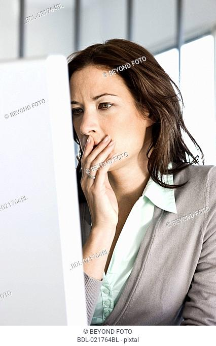 portrait of worried businesswoman looking at computer screen