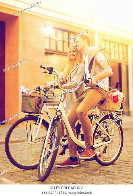 summer holidays, bikes, love, relationship and dating concept - couple with bicycles in the city