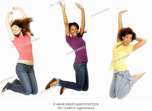 Three teenage girls jumping in the air with arms up, on solid white background