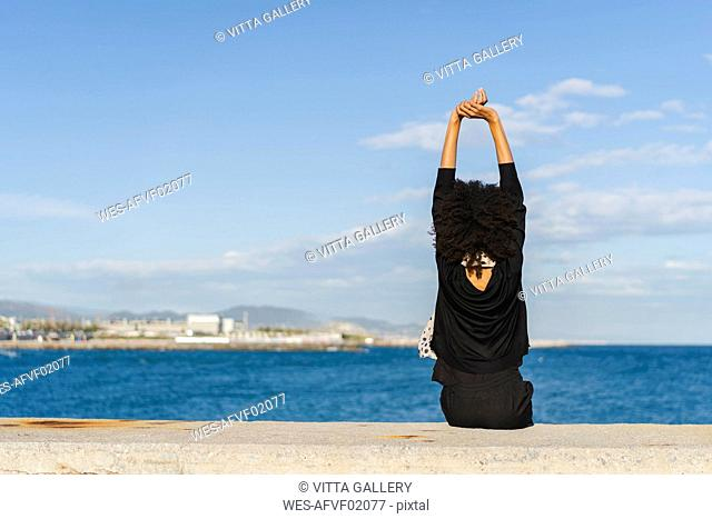 Spain, Barcelona, back view of woman dressed in black sitting on wall looking at the sea