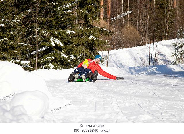Man and son tobogganing in snow covered forest
