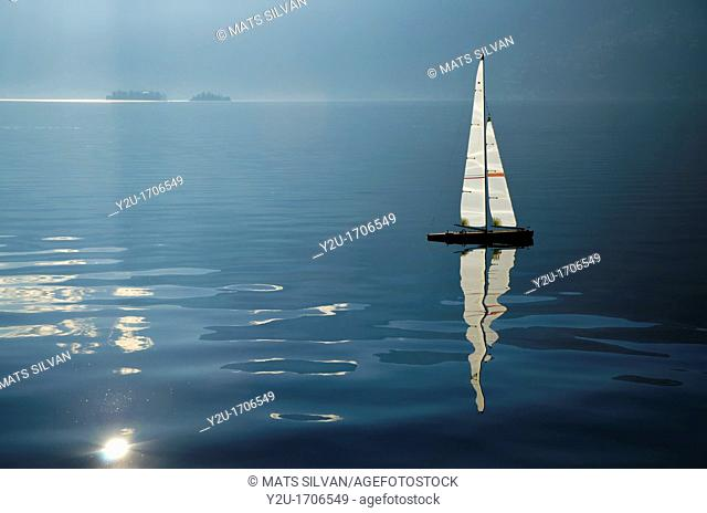 Sailing boat on an alpine lake with islands and reflections