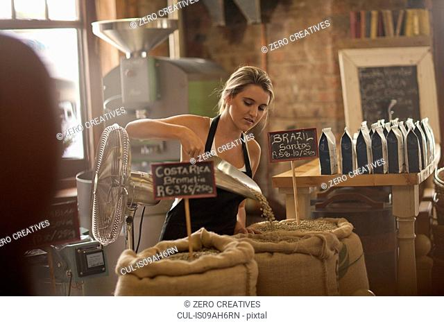 Young woman working in coffee shop, scooping coffee