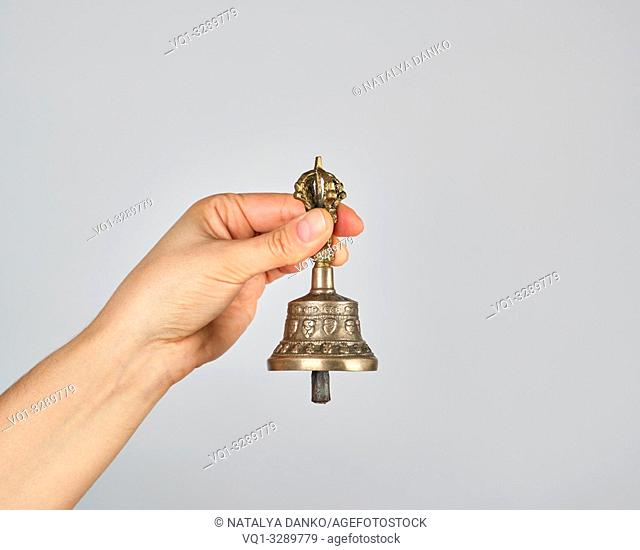 female hand holding a bronze bell for alternative medicine, meditation and relaxation