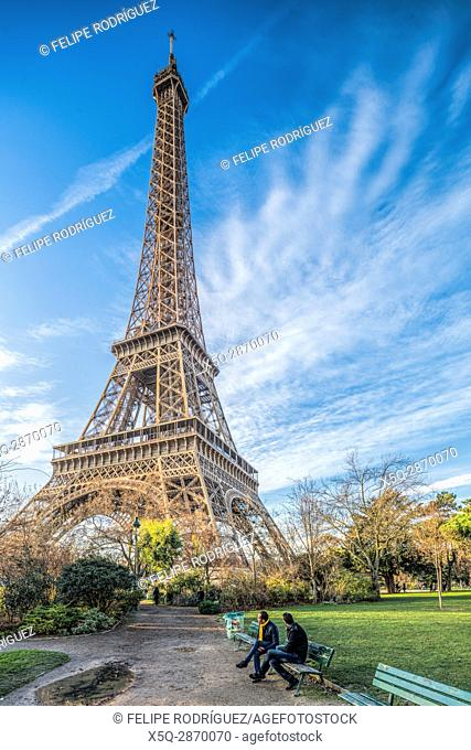 Two men sitting on a bench in front of the Eiffel Tower, Paris, France