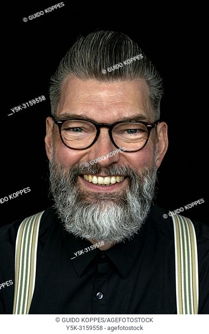 Tilburg, Netherlands. Studio portrait of a mid adult, caucasian, male hipster with moustache and beard