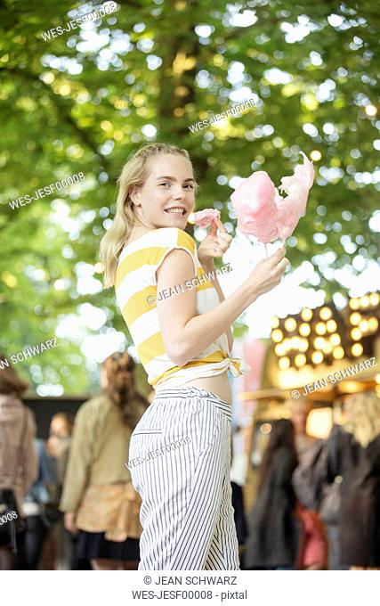 Portrait of young woman with pink candy floss on streetfood festival