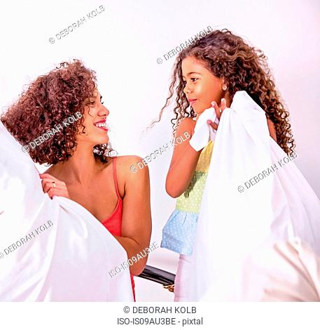 Mother and daughter holding pillows face to face smiling