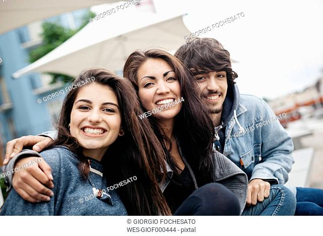 Italy, Rimini, portrait of three happy friends embracing outdoors
