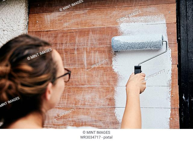 A woman using a paint roller, painting wooden planks on a wall