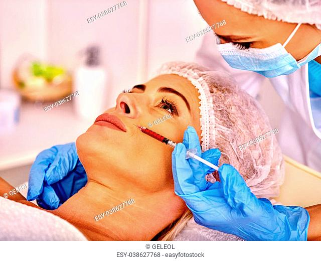 Woman middle-aged in spa salon with beautician. Female giving lips botox injections