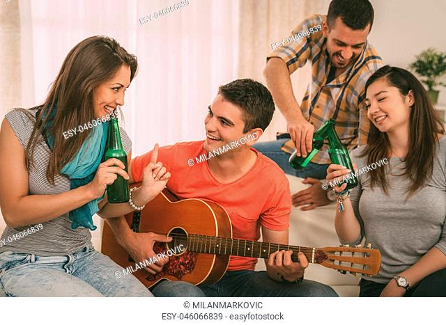 Four cheerful friends enjoing with guitar and beer in an apartment