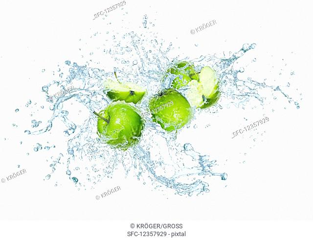 Green apples with water splash