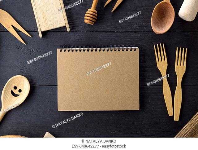 open notebook with blank pages in the middle of wooden kitchen items on a black table
