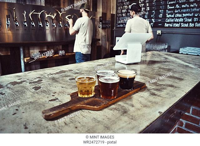 Tray with a selection of craft beers in a bar, two waiters in the background