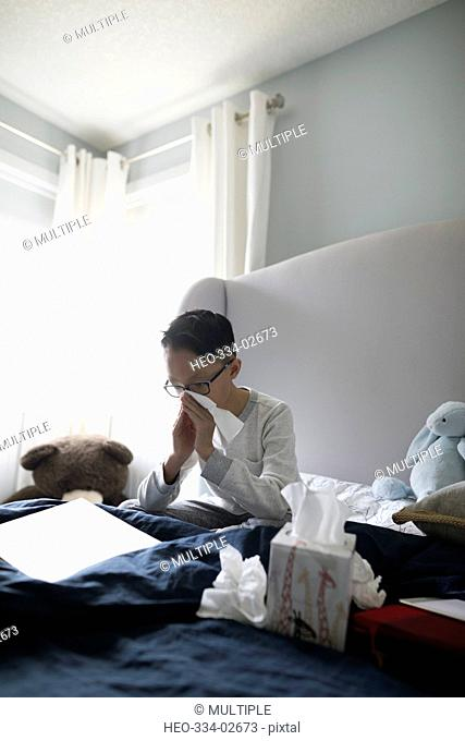 Boy with cold blowing nose with tissue on bed