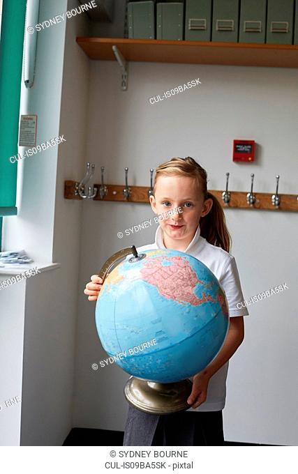Schoolgirl holding globe in classroom at primary school, portrait