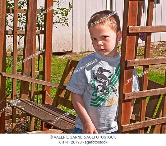 This Caucasian 5 year old boy is sad and upset as he's leaning against a cedar swing outside His eyes and facial expression and body language convey deep...