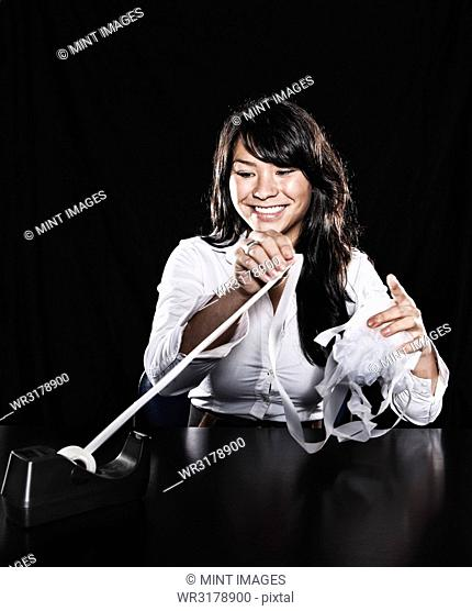 Studio portraits of an Asian woman with sticky tape tangled in her fingers