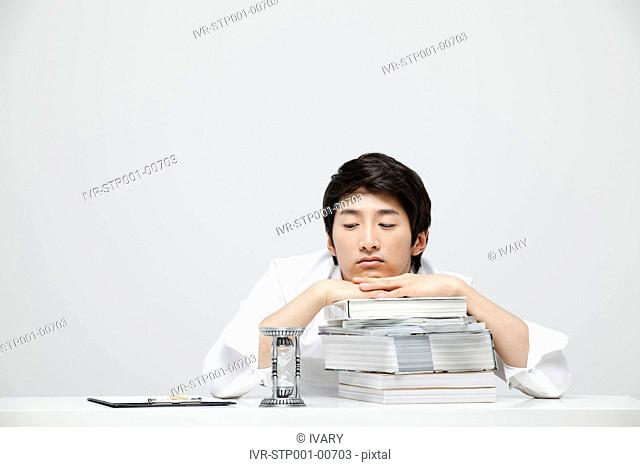 Asian Businessman Looking At Hour Glass And Leaning Head On Books At Work