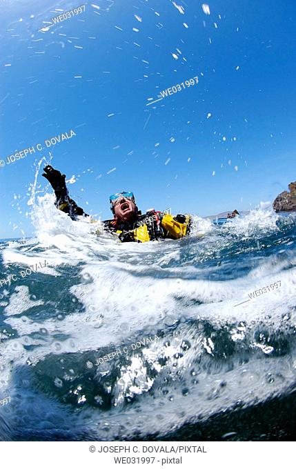 Male scuba diver in extreme panic at surface