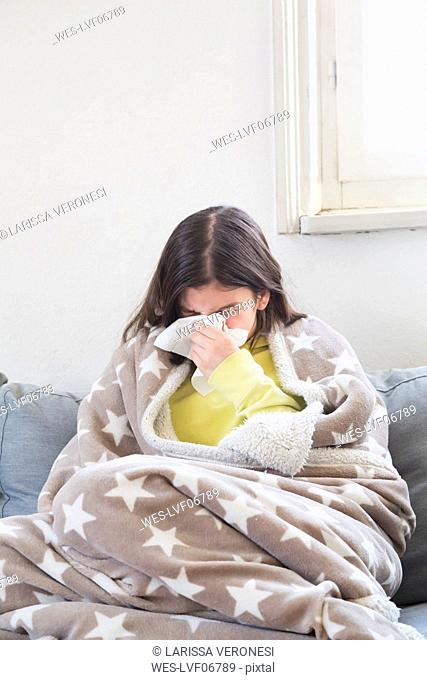 Girl having a cold sitting on the couch at home blowing nose