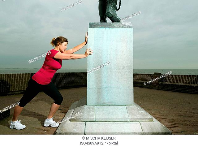 Woman stretching against statue