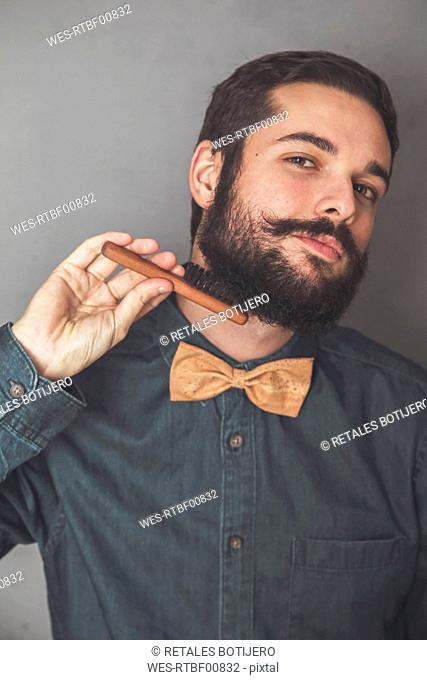Man combing his beard with a wooden brush, wearing denim shirt and cork bow tie