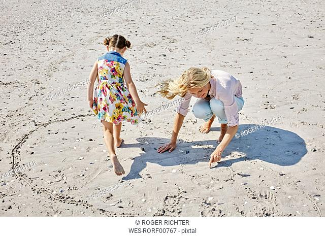 Mother and daughter drawing heart on the beach