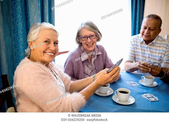 Smiling senior friends playing cards while having coffee