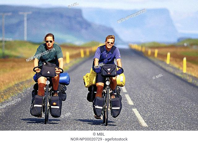 Two men cykling on the road