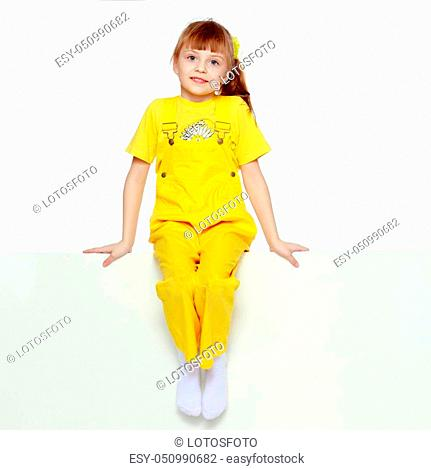 Girl with a short bangs on her head and bright yellow overalls. She crouched down on the white advertising banner