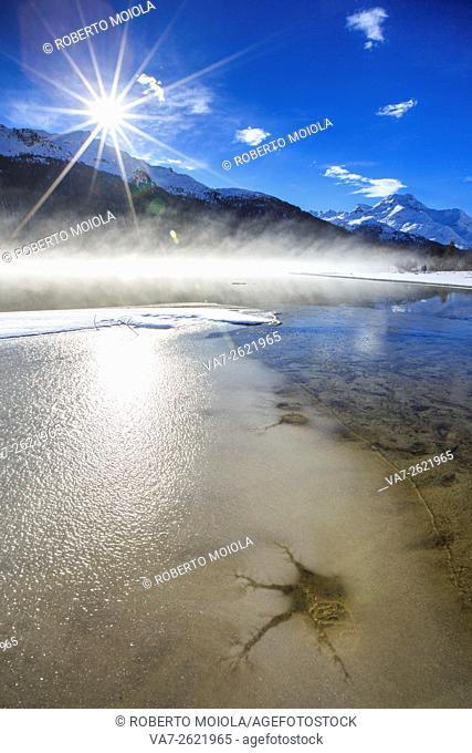 Winter sun light up the frozen Lake Silvaplana surrounded by mist Maloja Canton of Graubünden Engadine Switzerland Europe