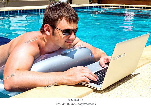 Businessman working with laptop in pool on the inflatable mattress