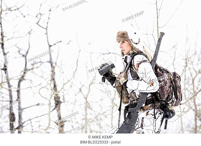 Caucasian woman hunting in forest using binoculars