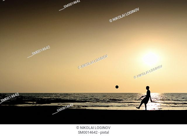Young man playing football silhouette ocean horizon sunset horizontal illustration
