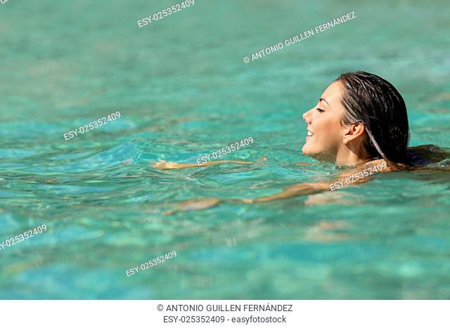 Woman swimming in a tropical sea on summer holidays with turquoise water in the background