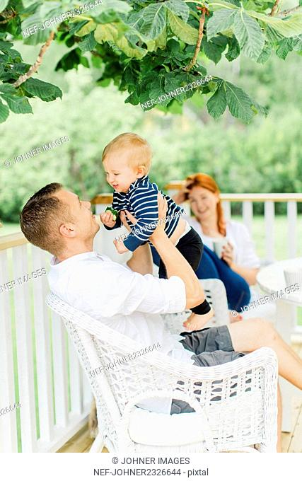 Parents with baby boy resting on balcony
