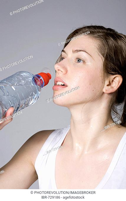 Young woman drinking from a bottle of water during workout