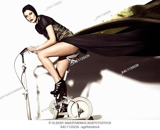 Young woman in a beautiful flying in the wind long dress posing on a retro exercise bike  Edgy high fashion photo