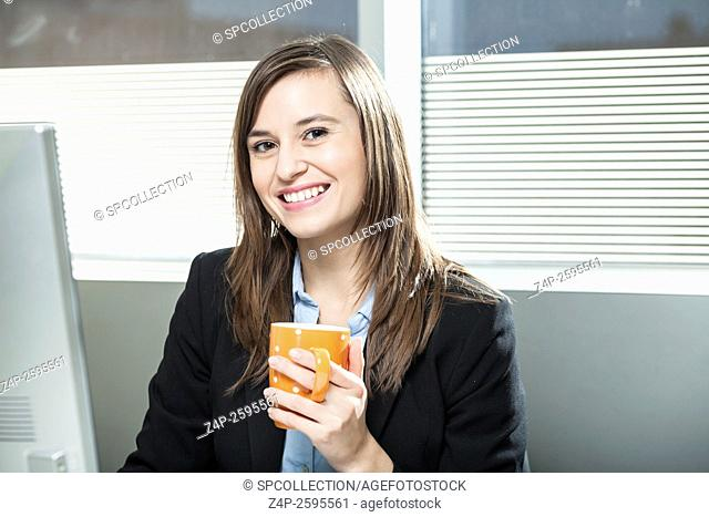 Woman in office with coffee looking at camera