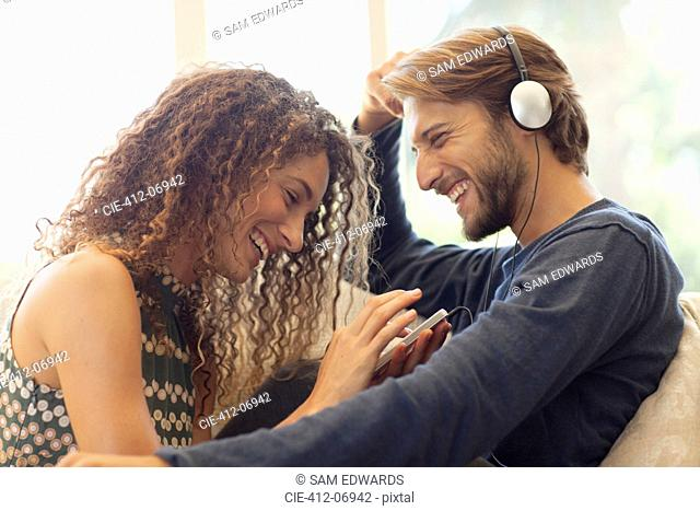 Couple listening to headphones on sofa