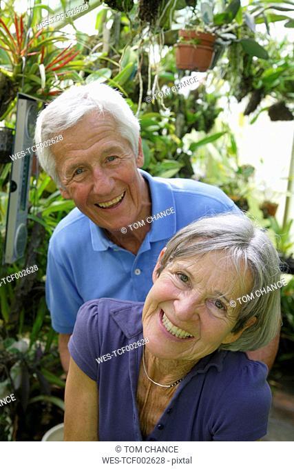 Germany, Bavaria, Senior couple in glass house, portrait